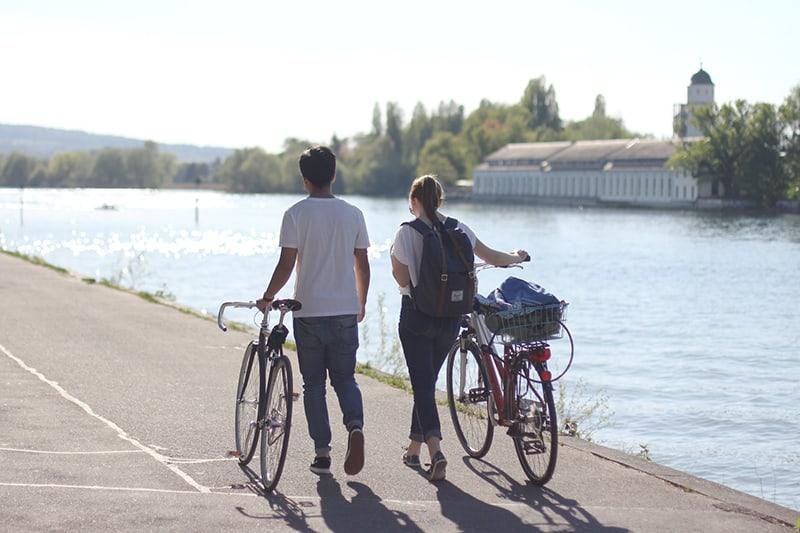 Ein Mann und eine Frau gehen und halten ihre Fahrräder in der Nähe des Flusses, während sie Zeit miteinander verbringen