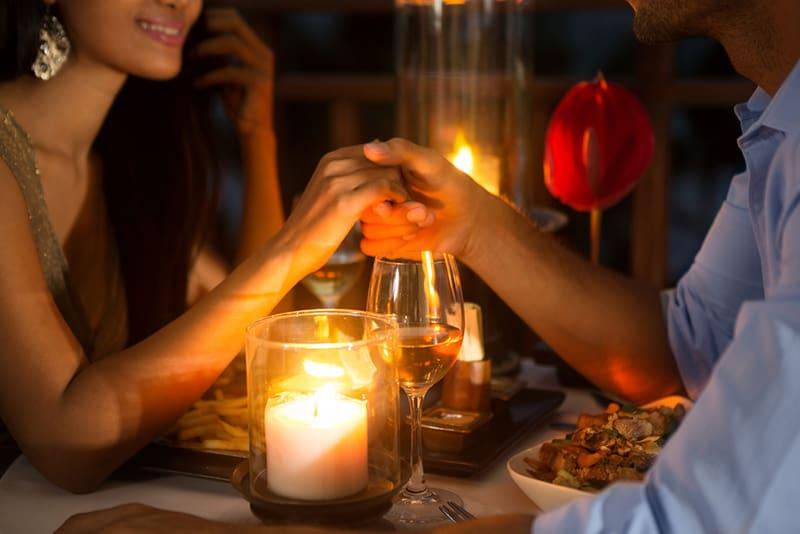 Ein Mann und eine Frau halten sich bei romantischem Abendessen bei Kerzenlicht die Hände zusammen