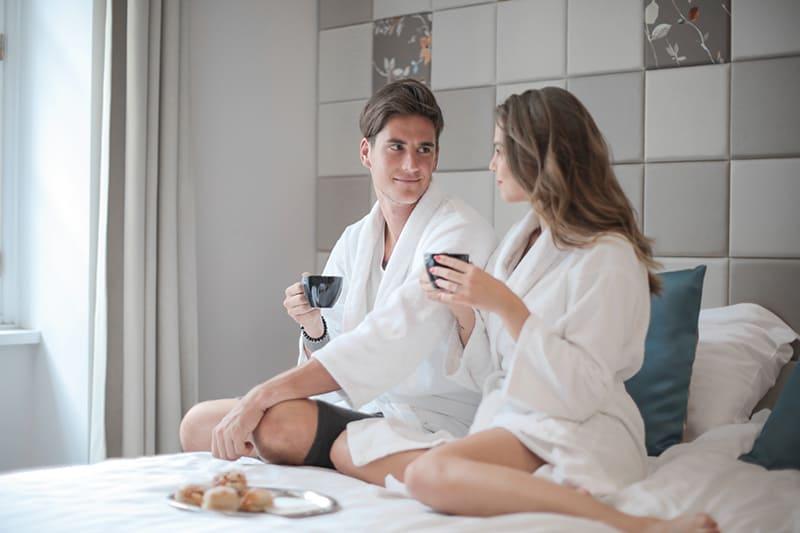 Ein Mann und eine Frau im weißen Bademantel schauen sich beim Frühstück im Bett an