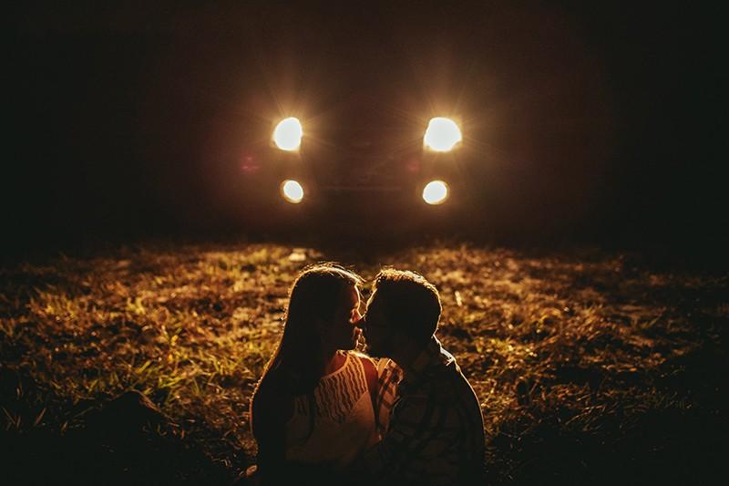 Ein Mann und eine Frau küssen sich, während sie im Gras vor dem Auto sitzen und nachts Licht an haben