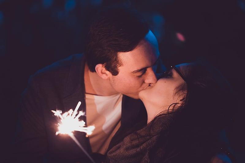 ein Mann und eine Frau küssen und halten Feuer Wunderkerze