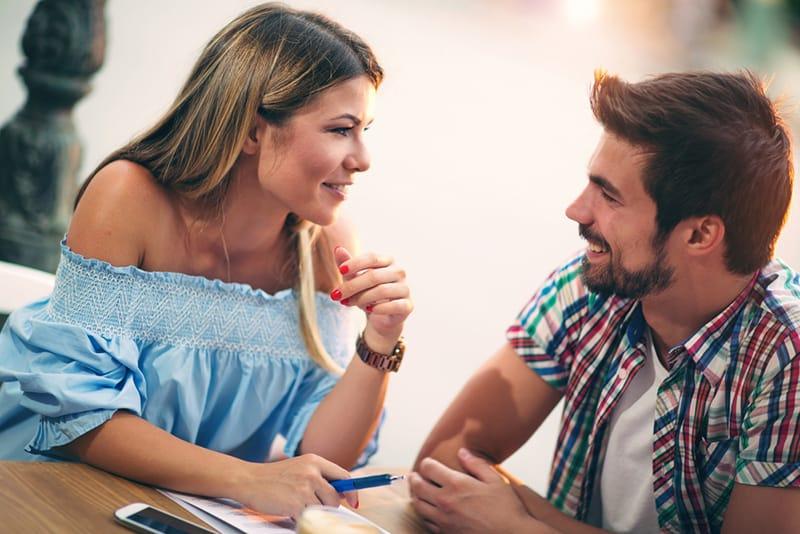 Ein Mann und eine Frau lächeln während des Gesprächs, während sie im Café sitzen