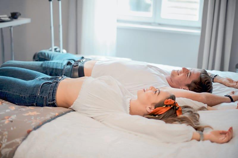 Ein Mann und eine Frau liegen mit ausgebreiteten Armen auf einem Bett