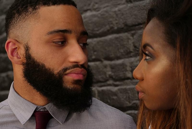 Ein Mann und eine Frau sehen sich an, während sie in der Nähe einer Mauer stehen