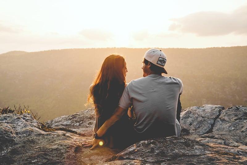 Ein Mann und eine Frau schauen sich an, während sie während des Sonnenuntergangs auf der Klippe sitzen