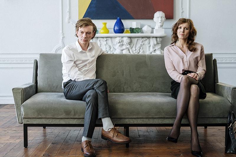 Ein Mann und eine Frau, die verwirrt aussehen, sitzen auf dem Sofa