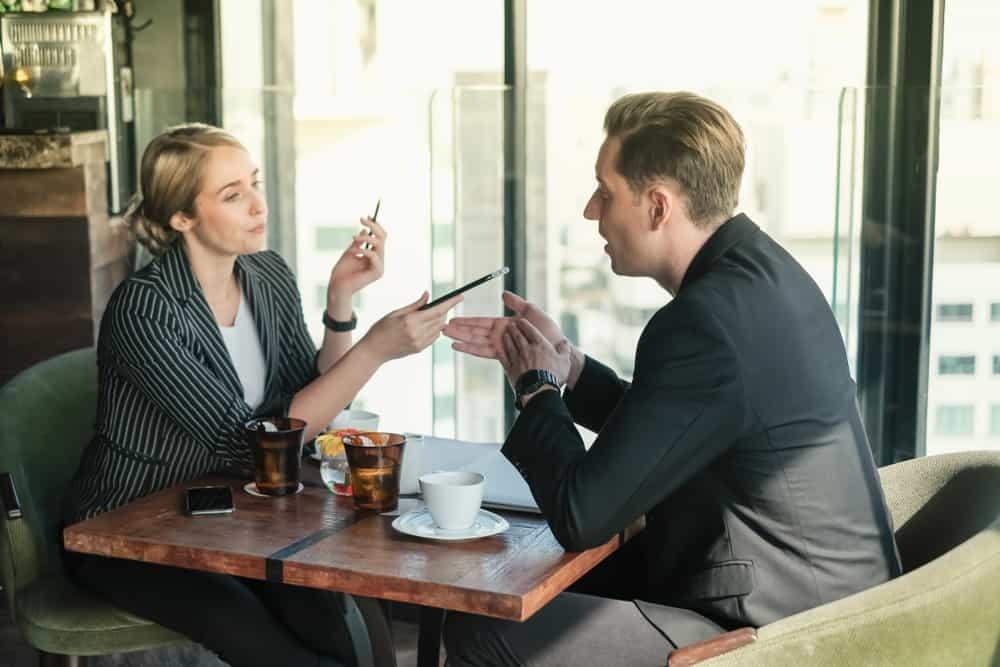 Ein Mann und eine Frau sitzen an einem Tisch und streiten sich