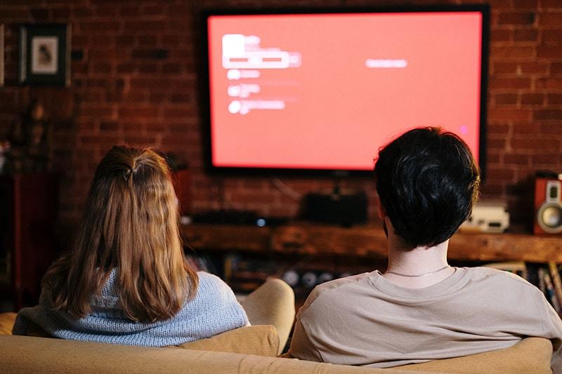 Ein Mann und eine Frau sitzen auf der Couch vor dem Fernseher