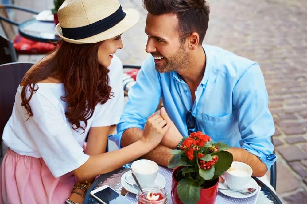 Ein Mann und eine Frau sitzen, trinken Kaffee und halten sich an den Händen