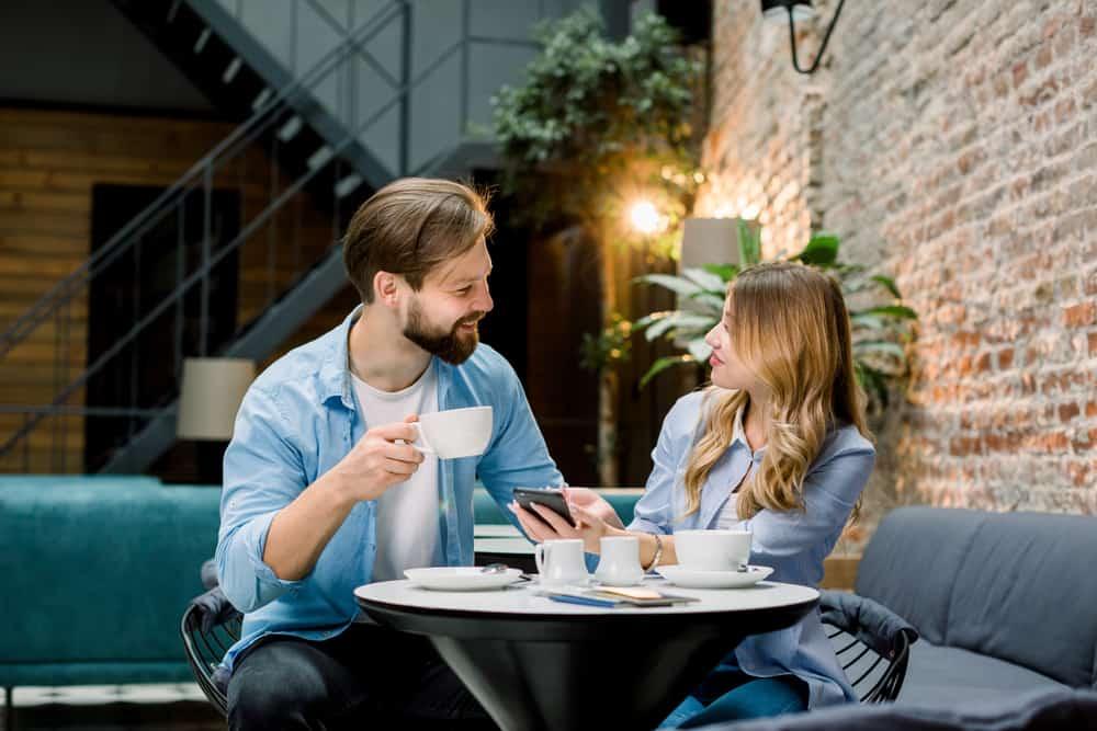 Ein Mann und eine Frau sitzen, trinken Kaffee und reden