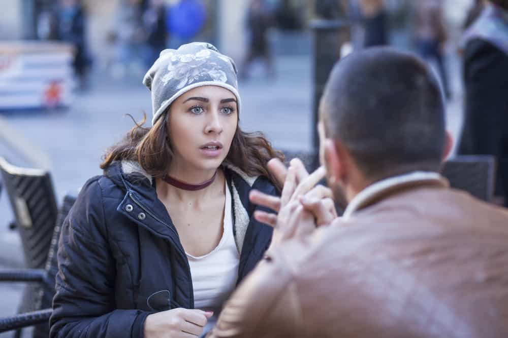 Ein Mann und eine Frau sitzen und streiten sich auf der Terrasse eines Cafés