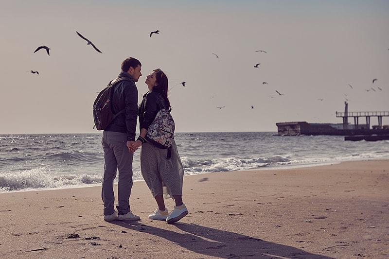 Ein Mann und eine Frau stehen am Strand und wollen sich küssen
