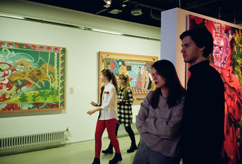 Ein Mann und eine Frau stehen in der Galerie und schauen sich eine Kunstausstellung an