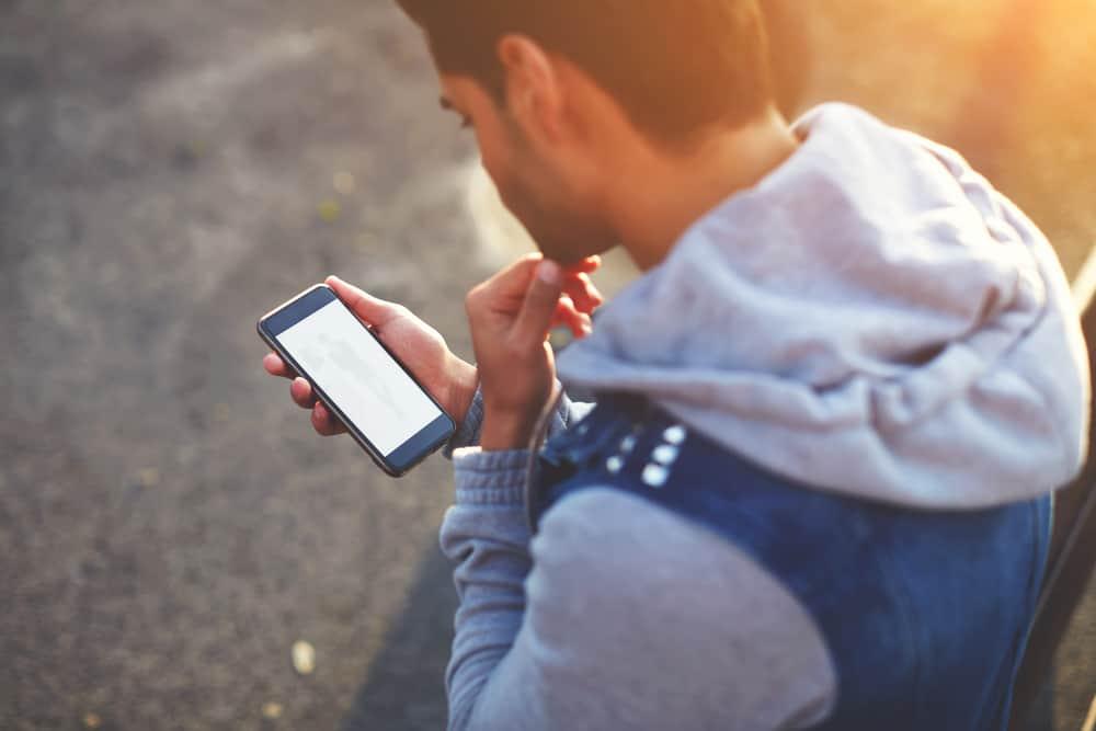 Ein dunkelhäutiger Mann benutzt ein Handy