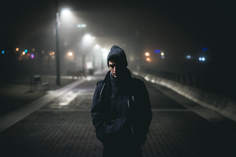 Ein einsamer Mann geht nachts die Straße entlang