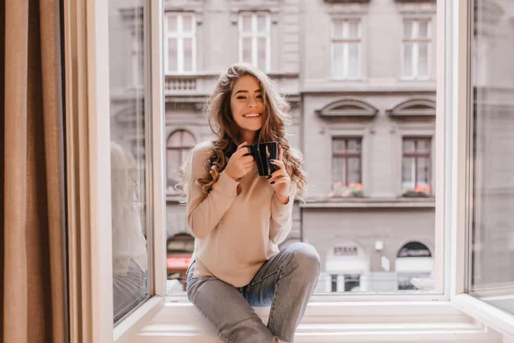 Ein glückliches Mädchen mit schönen langen Haaren sitzt am Fenster und trinkt Kaffee