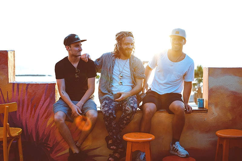 ein introvertierter Mann, der ein schwarzes T-Shirt trägt mit zwei Freunden auf der Veranda sitzen, während Freunde Spaß haben
