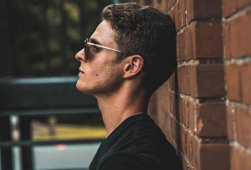 Ein-junger-Mann-mit-Brille-lehnte-an-einer-Wand(1)
