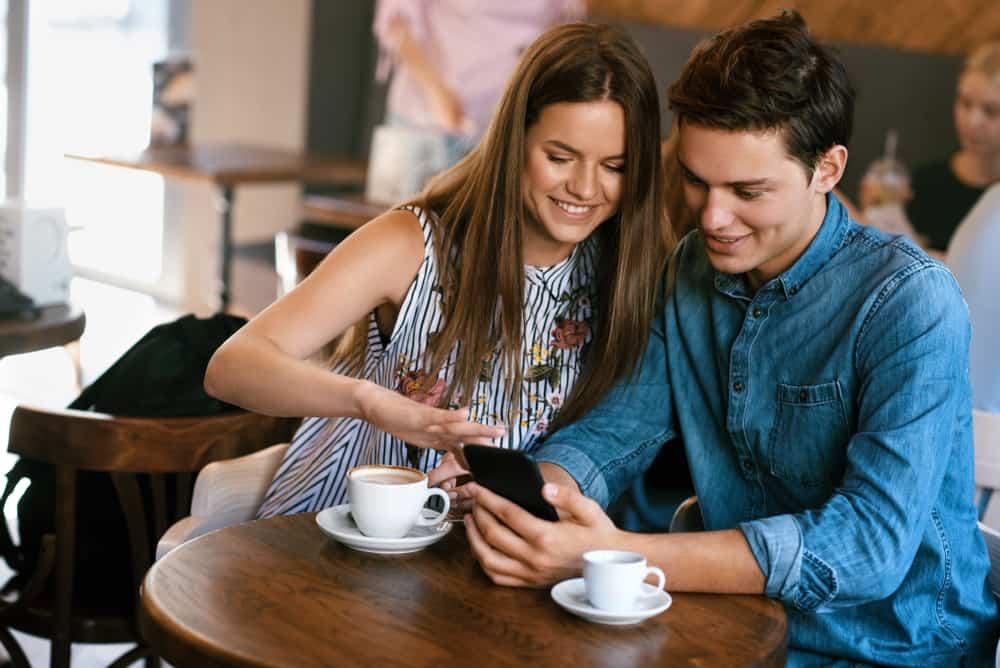 Ein junges Liebespaar sitzt in einem Café und schaut sich etwas auf ihrem Handy an