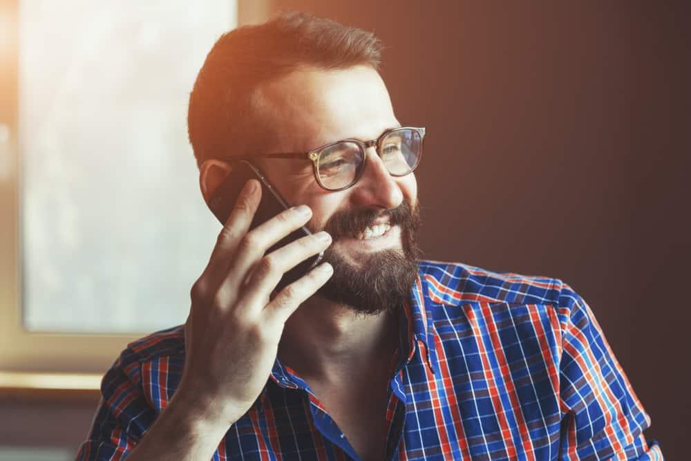 Ein lächelnder Mann mit Bart sitzt und spricht auf seinem Handy