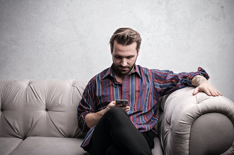 ein lächelnder Mann, der auf dem Smartphone eine SMS schreibt, während er auf der Couch sitzt
