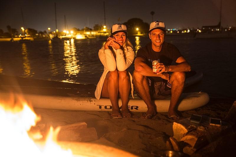 Ein lächelnder Mann und eine lächelnde Frau sitzen an der Küste in der Nähe des Freudenfeuers