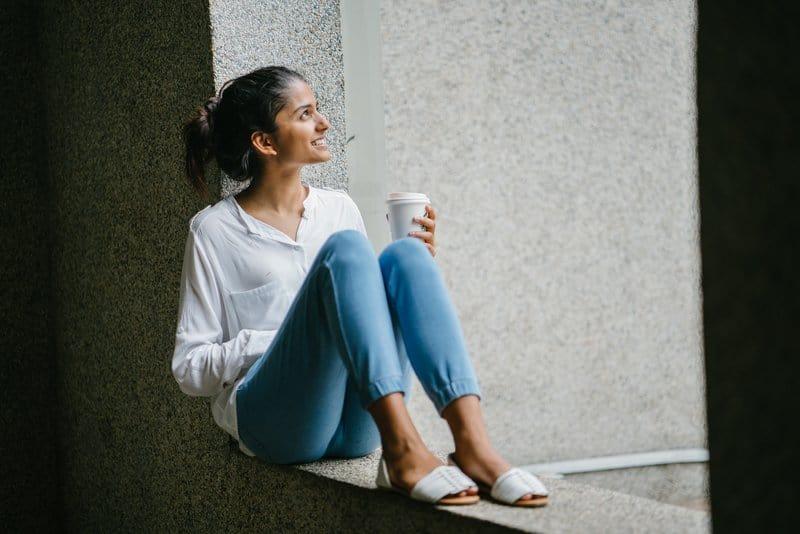 Ein lächelndes Mädchen mit Kaffee in der Hand sitzt auf der Terrassenwand