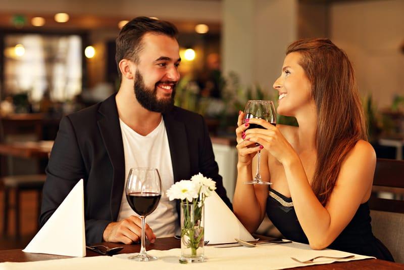 ein lächelndes Paar, das während eines Dates Wein im Restaurant trinkt