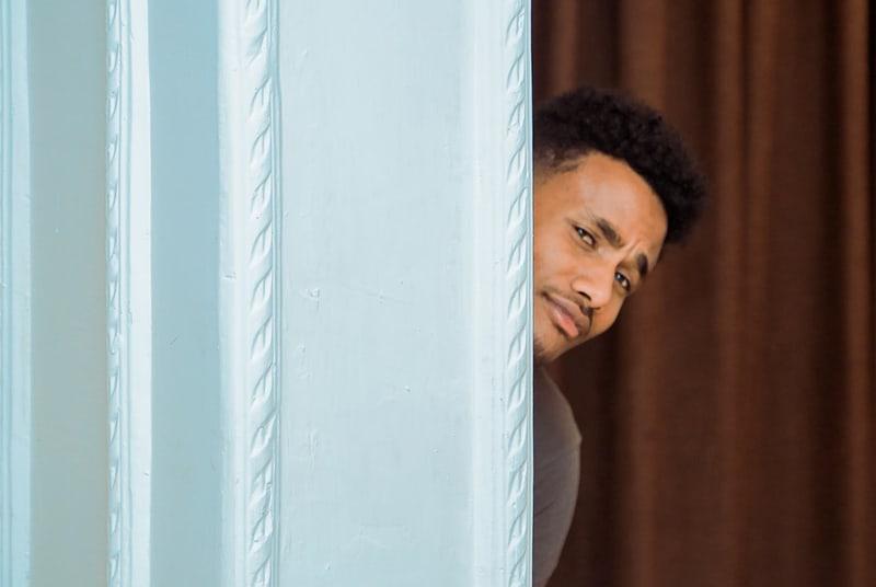 Ein schüchterner Mann spähte durch die Tür, während er in der Nähe eines braunen Vorhangs stand