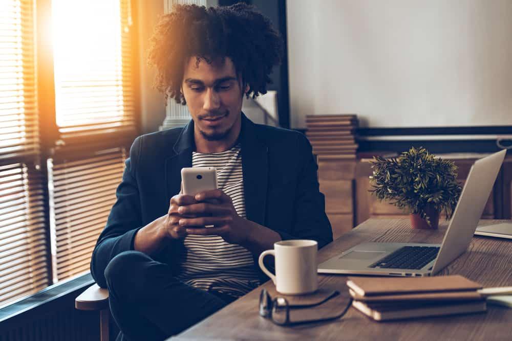 Ein schwarzer Mann sitzt an seinem Schreibtisch und schreibt eine SMS