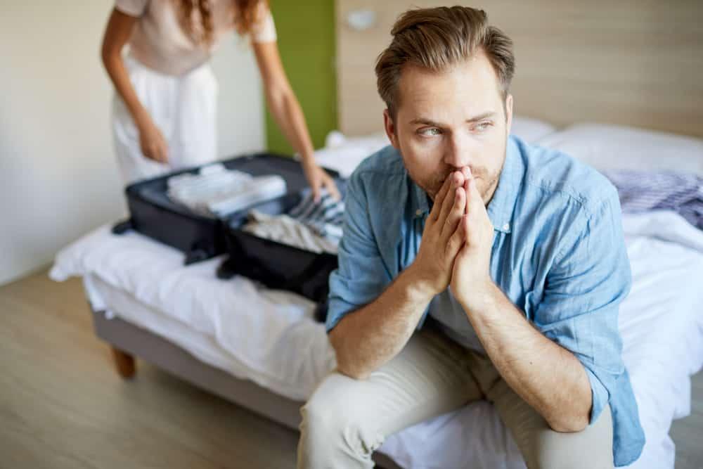 Ein trauriger Mann sitzt auf dem Bett, während eine Frau Sachen packt und ihn verlässt
