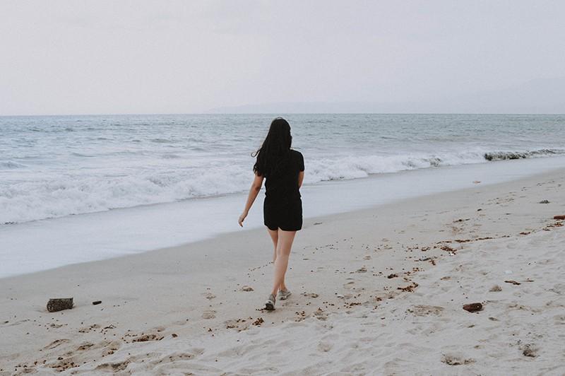 Eine Frau, die tagsüber allein an der Küste spazieren geht