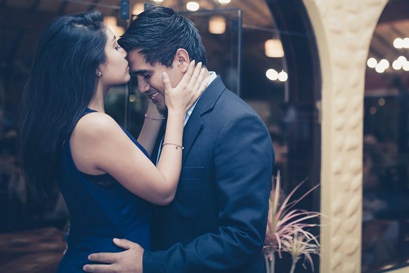 Eine Frau küsste einen Mann auf die Stirn, während sie abends vor dem Gebäude stand