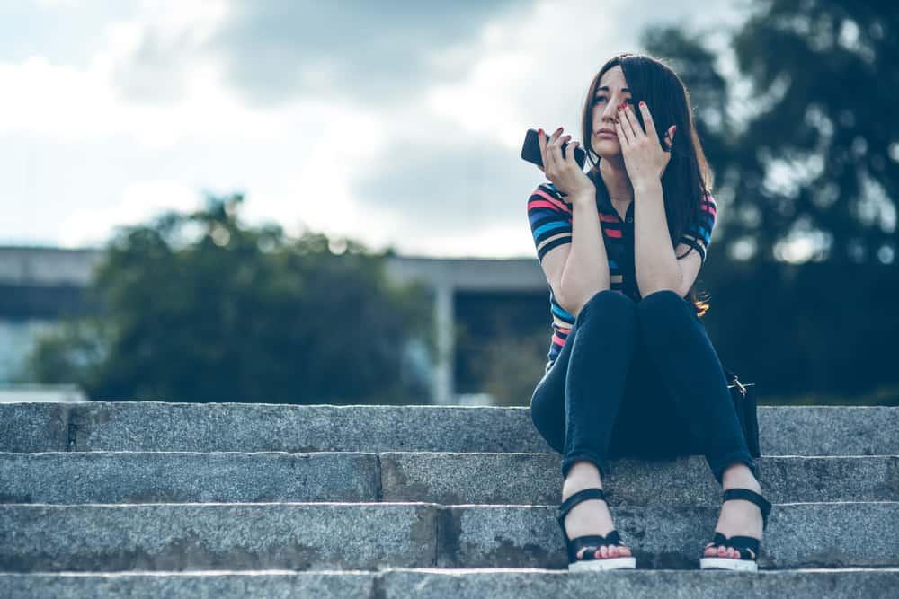 Eine Frau mit einem Handy in der Hand sitzt auf der Treppe und weint
