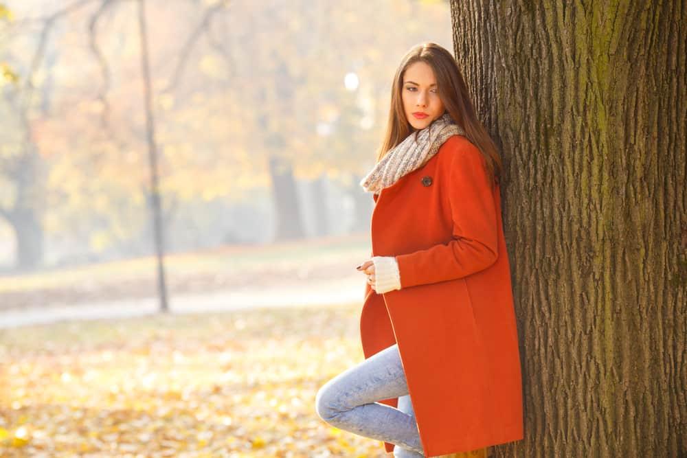 Eine Frau mit traurigem Gesicht steht an einen Baum im Park gelehnt