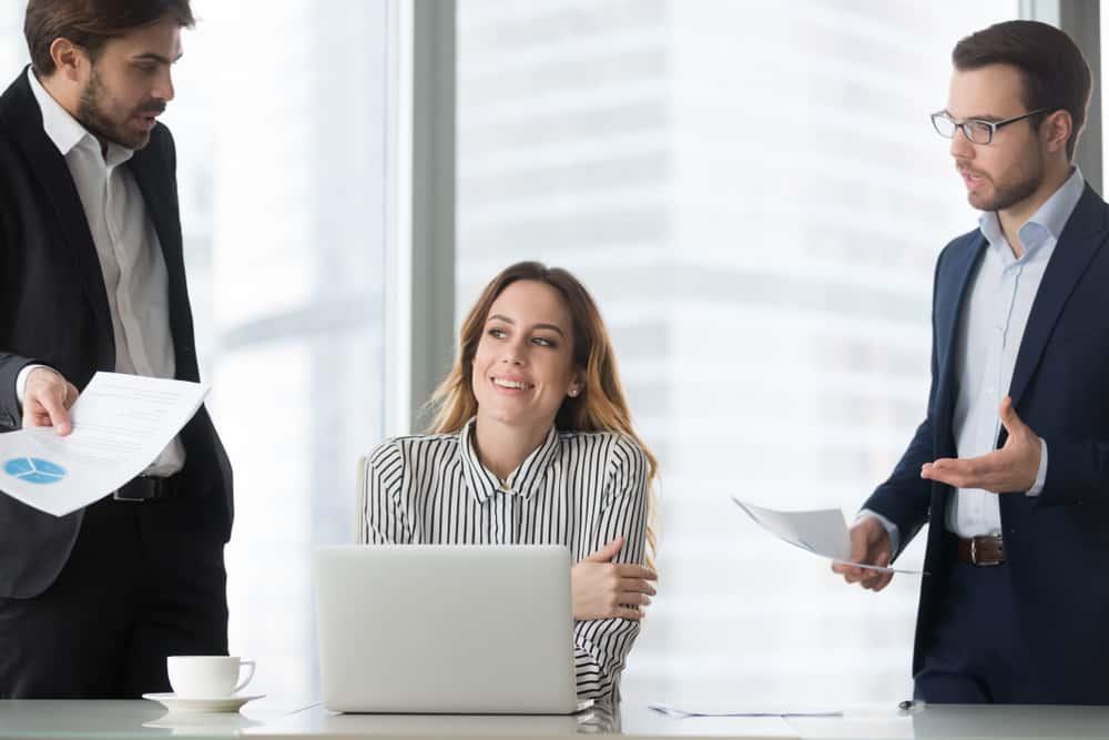 Eine Geschäftsfrau im Büro sitzt und ignoriert zwei Kollegen mit einem Lächeln
