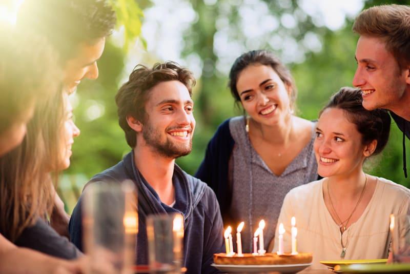 Eine Gruppe junger Leute versammelte sich auf einer Terrasse, um den Geburtstag eines ihrer Freunde zu feiern