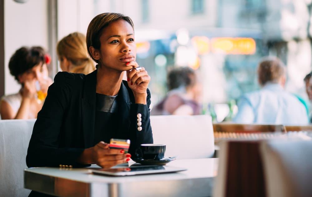 Eine besorgte Frau mit einem Handy in der Hand sitzt in einem Café