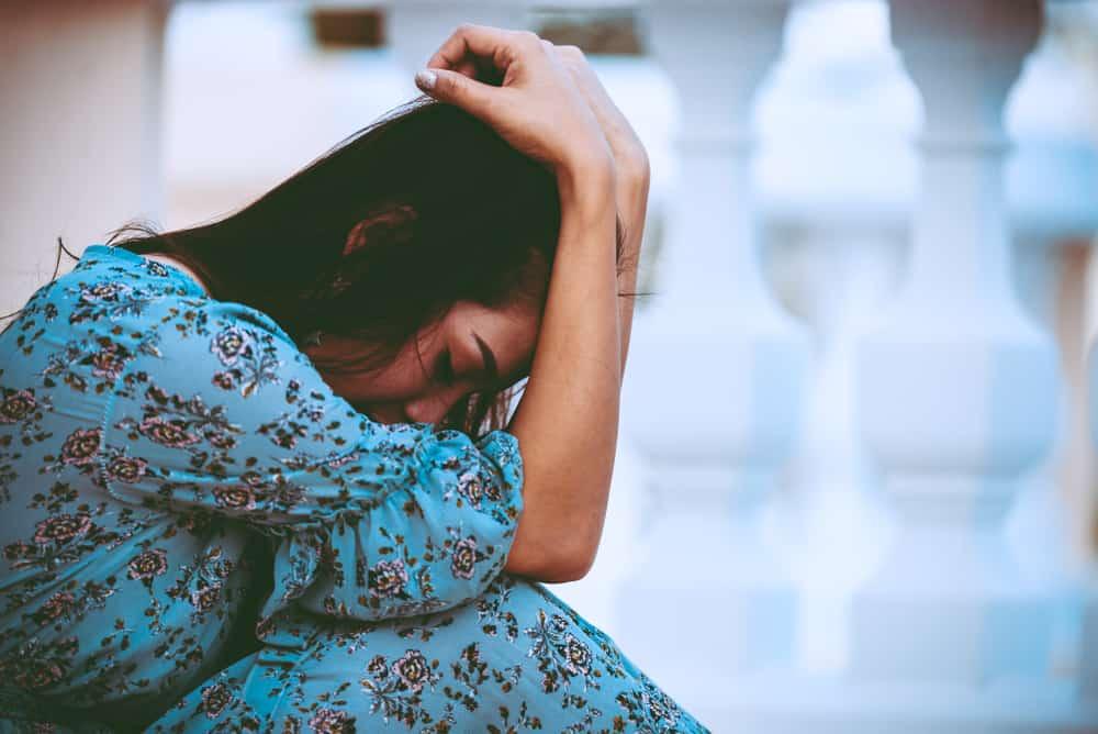 Eine depressive Frau in einem blauen Kleid sitzt zusammengerollt auf dem Balkon