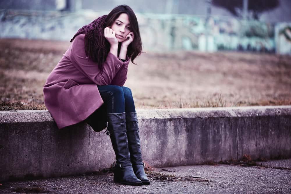 Eine enttäuschte Frau in einem lila Mantel sitzt auf einer Betonwand