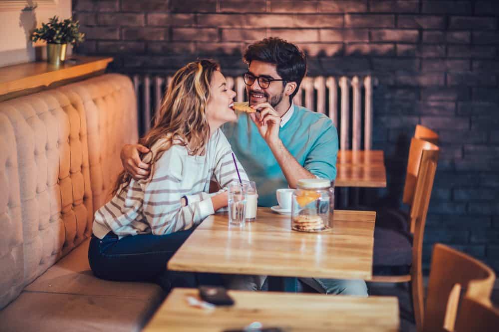 Eine glückliche Frau isst in einem Café einen Keks aus der Hand ihres Mannes