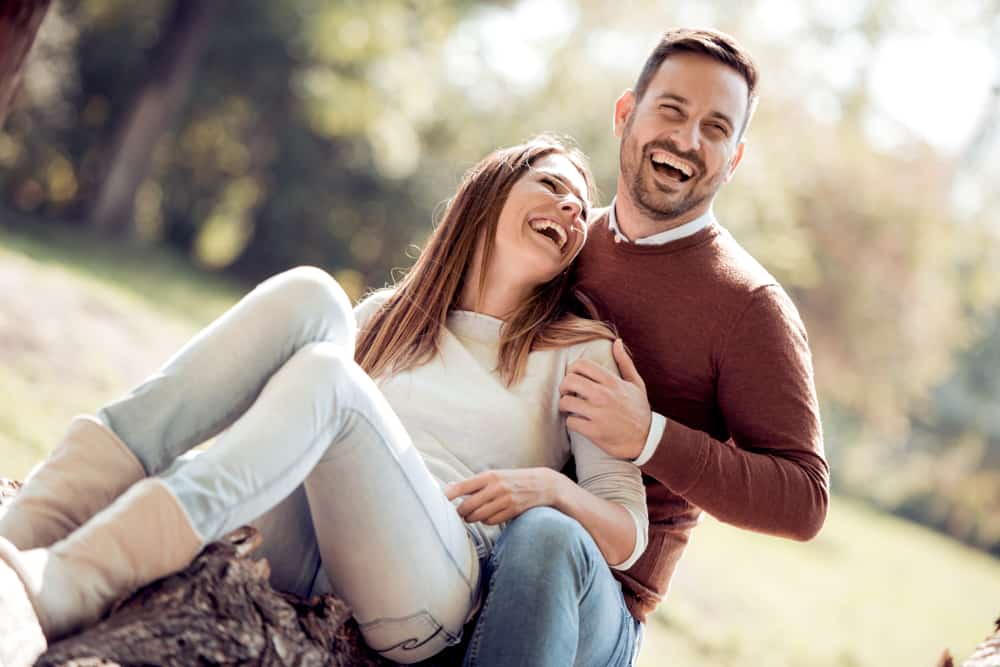 Eine glückliche Frau sitzt in den Armen ihres lächelnden Mannes
