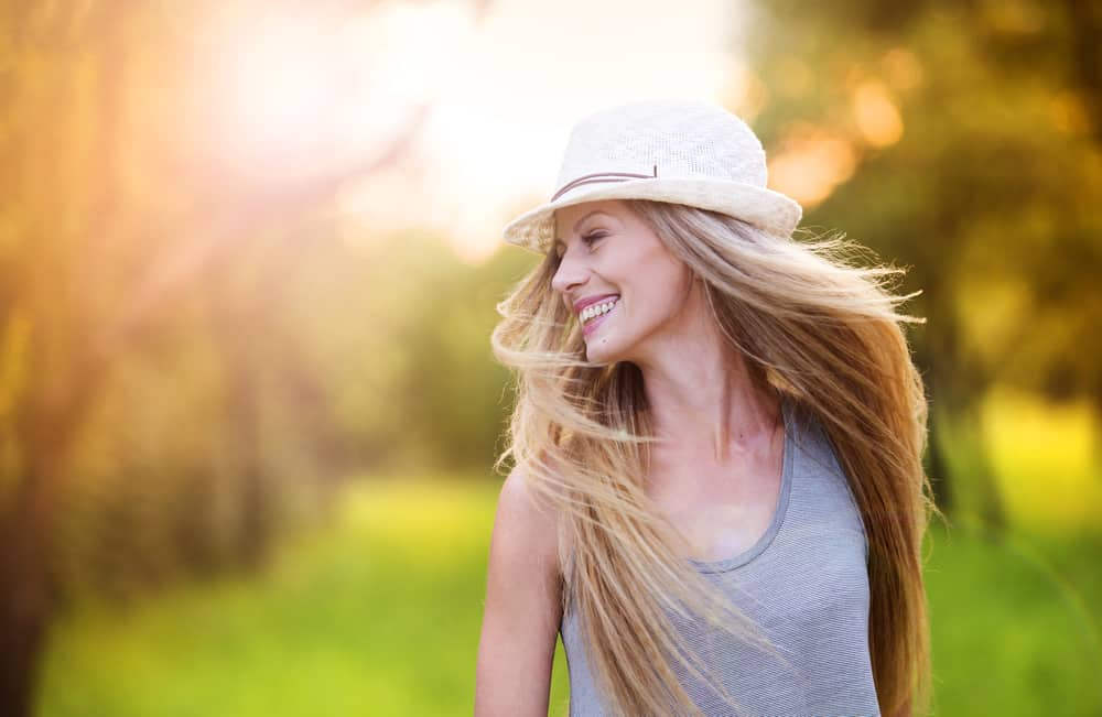 Eine lächelnde Blondine mit Hut geht in den Park