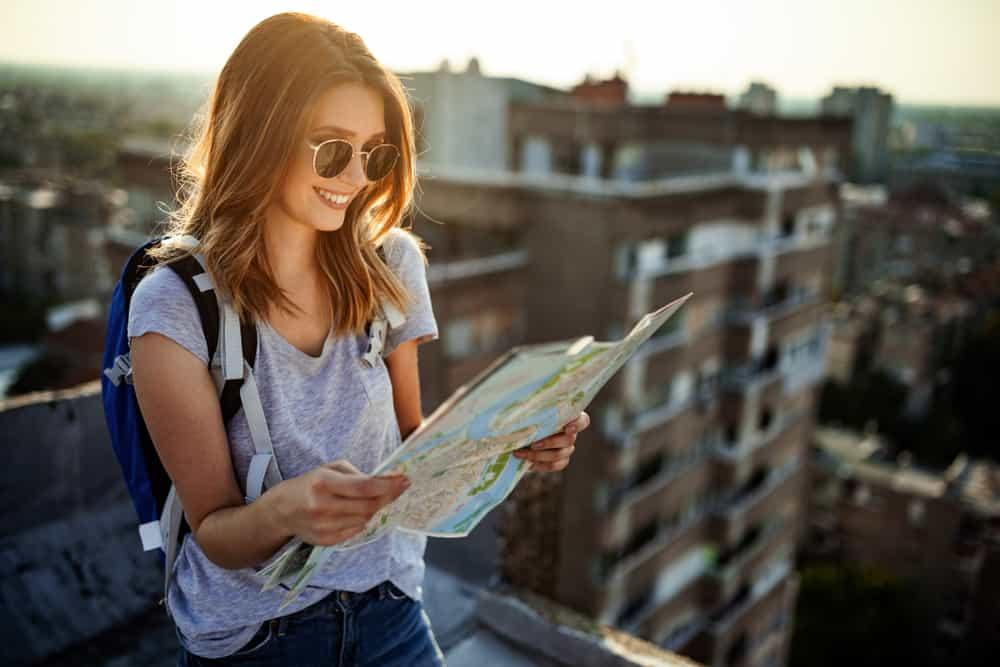 Eine lächelnde Frau steht auf dem Dach des Gebäudes und schaut auf eine Karte