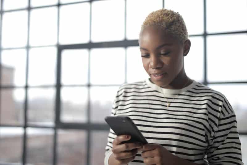 Eine lächelnde kurzhaarige schwarze Frau benutzt ein Smartphone