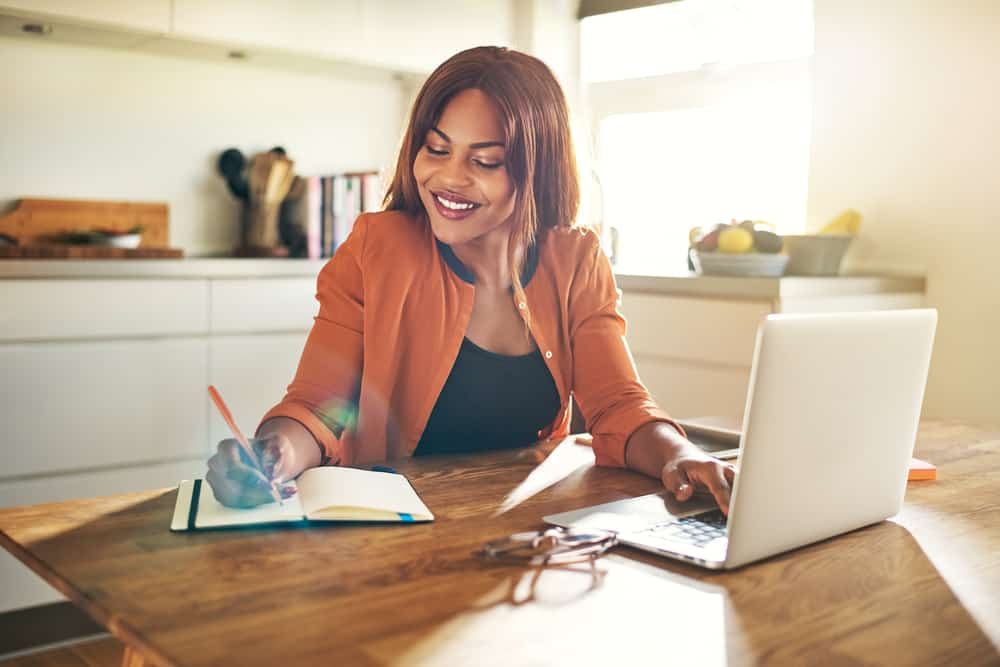 Eine lächelnde schwarze Frau arbeitet von zu Hause aus an einem Laptop