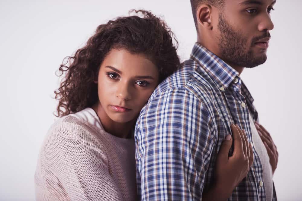 Eine schöne Afroamerikanerin umarmt ihren Mann von hinten
