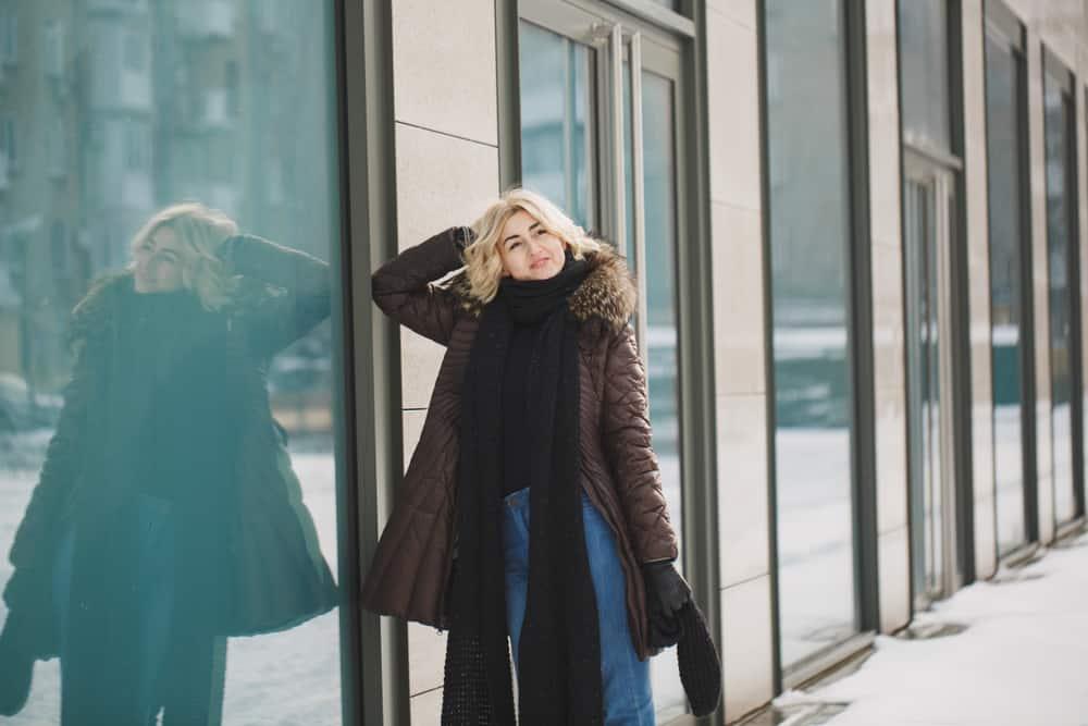 Eine schöne Blondine in einer Winterjacke steht neben einem Schaufenster