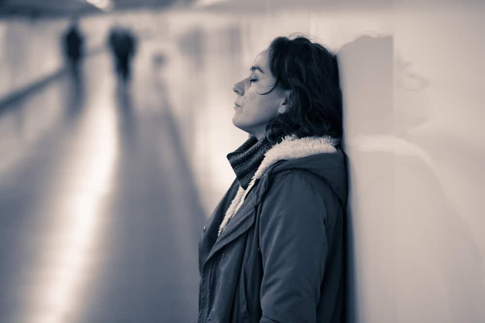 Eine traurige Frau in der Unterführung steht an der Wand gelehnt