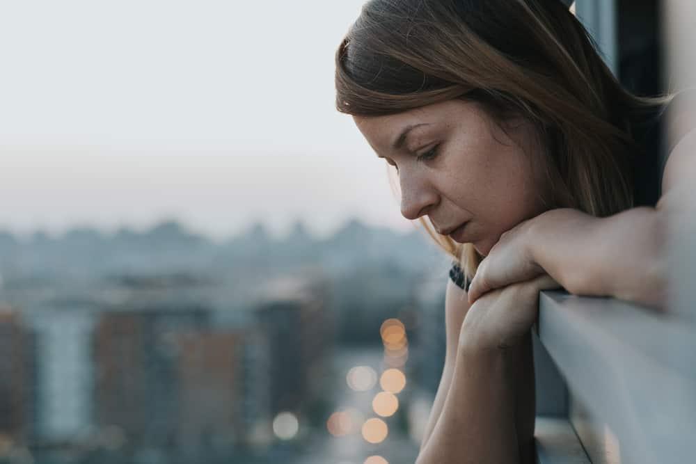 Eine traurige Frau lehnt sich an das Balkongeländer und schaut nach unten